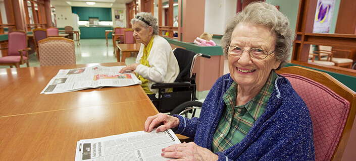 Senior citizen reading the news paper smiling